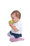 Young baby girl eating fresh green apple Stock Image