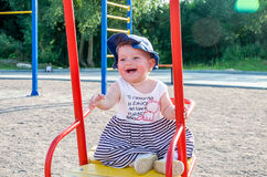 Young baby girl happy family playing on the swing, and ride in the amusement park smiling Royalty Free Stock Image