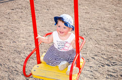 Young baby girl happy family playing on the swing, and ride in the amusement park smiling Royalty Free Stock Photos