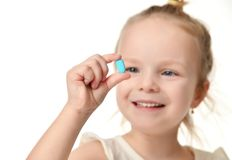 Young baby girl hold light blue headache  pill medicine tablet in small hand. Isolated on a white background Royalty Free Stock Images