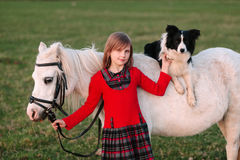Young baby girl. Red dress. Dog on horseback. Little White Horse pony royalty free stock images