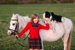 Young baby girl. Red dress. Dog on horseback. Little White Horse pony. Outdoors Stock Image