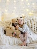 Young baby girl sitting dreaming near magical New year craft gifts by a Christmas tree Stock Photos