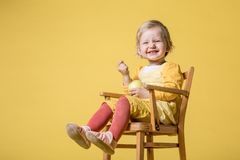 Young Baby Girl in Yellow Dress on Yellow Background royalty free stock photography