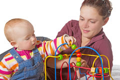Young baby learning muscle coordination. Baby with motor activity development delay being stimulated to develop muscle coordination and movement on a bead maze Royalty Free Stock Photo