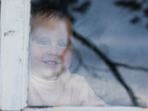 Young baby looking from window Stock Photography