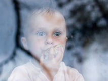 Young baby looking from window Royalty Free Stock Photos