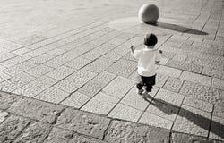 Young baby running towards stone ball Stock Photo