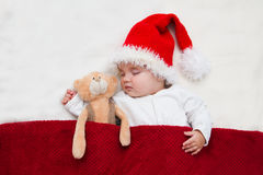 Young baby in a Santa Claus hat. Sleeping Christmas baby and Teddie's bear wearing Santa hats Stock Image