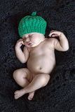 Young baby sleeping. A young baby girl with green cap sleeping on black wool Royalty Free Stock Images