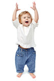 Young baby standing indoors applauding and smiling. The child dances on a white background, indulge in, runs, plays, hands up stock photos
