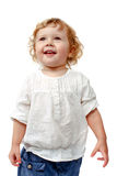 Young baby standing indoors applauding and smiling. The child dances on a white background, indulge in, runs, plays, hands up stock photo
