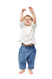 Young baby standing indoors applauding and smiling. The child dances on a white background, indulge in, runs, plays, hands up Stock Image