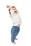 Young baby standing indoors applauding and smiling. The child dances on a white background, lifted his leg, walks, indulge in, runs, plays, hands up stock photography