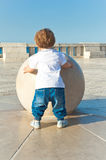 Young baby touch a big sphere, concept of growth Royalty Free Stock Photos
