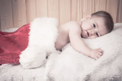 Young baby wearing a santa claus suit and hat in christmas in a barn Stock Image