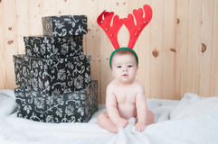 Young baby wearing a santa claus suit and hat in christmas in a barn Royalty Free Stock Photography