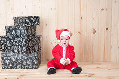 Young baby wearing a santa claus suit and hat in christmas in a barn Stock Photo