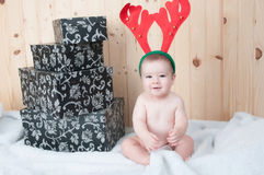 Young baby wearing a santa claus suit and hat in christmas in a barn. Very young baby wearing a santa claus suit and hat in christmas in a barn Stock Photography