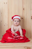 Young baby wearing a santa claus suit and hat in christmas in a barn. Very young baby wearing a santa claus suit and hat in christmas in a barn Royalty Free Stock Photography