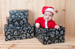Young baby wearing a santa claus suit and hat in christmas in a barn. Very young baby wearing a santa claus suit and hat in christmas in a barn Royalty Free Stock Images