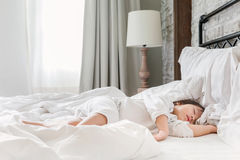 Young baby 2-3 year sleeping on the bed in morning. Sunrise, sleepy and lazy girl in the bedroom, sleeping child Stock Photo