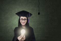 Young bachelor giving bright light bulb Stock Image