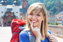 Young backpacker with blonde hair laughing at camera Stock Image