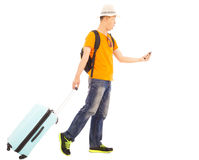 Young backpacker carrying a baggage and holding a smartphone Royalty Free Stock Photo