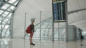 Young backpacker checking flight information on digital schedule display