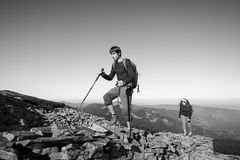 Young backpacker couple walking up rocky the mountain top Royalty Free Stock Photography