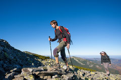 Young backpacker couple walking up rocky the mountain top Stock Photos