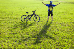 Young backpacker relaxing on a meadow with bicycle Royalty Free Stock Photo