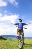 Young backpacker sitting on a  mountain bike and relaxing pose Royalty Free Stock Image