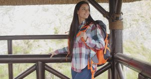 Young backpacker standing on a mountain lookout stock footage