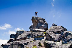 Young backpacker standing on top of a mountain Royalty Free Stock Photo