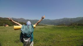 Young backpacker standing on top of a mountain and enjoying a morning valley view stock footage