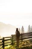 Female hiker enjoys beautiful mountain scenery at dawn in carpathian rural area stock image