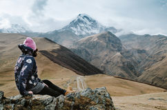 Young backpacker woman sitting on a rock in caucasus mountains. Young backpacker woman sitting on a rock with Kazbek mountain in the background Royalty Free Stock Photography