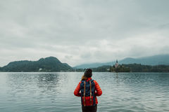 Young backpacker woman standing by mountain lake with backpack Royalty Free Stock Photos
