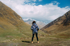 Young backpacker woman standing in the mountain valley Royalty Free Stock Photo