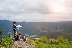 Young backpackers enjoying a valley view from top of a mountain Royalty Free Stock Photography