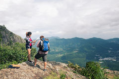 Young backpackers enjoying a valley view from top of a mountain Stock Images