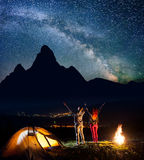 Young backpackers - guy and girl raised their hands up under the beautiful starry sky near campfire and tent Royalty Free Stock Images
