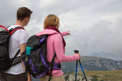 Young backpackers searching the destination in the mountains. While hiking royalty free stock photos