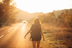 Young backpacking adventurous woman hitchhiking on the road.Ready for adventure of life.Travel lifestyle.Low budget traveling.Adve. Nturous active vacations Stock Photos