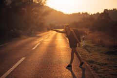 Young backpacking adventurous woman hitchhiking on the road.Ready for adventure of life.Travel lifestyle.Low budget traveling.Adve. Nturous active vacations Royalty Free Stock Photography