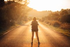 Young backpacking adventurous woman hitchhiking on the road.Ready for adventure of life.Travel lifestyle.Low budget traveling.Adve. Nturous active vacations Royalty Free Stock Images