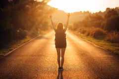 Young backpacking adventurous woman hitchhiking on the road.Ready for adventure of life.Travel lifestyle.Low budget traveling.Adve. Nturous active vacations Royalty Free Stock Photos