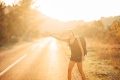 Young backpacking adventurous woman hitchhiking on the road.Stopping a car with a thumb.Travel lifestyle.Low budget traveling. Adventurous active vacations Stock Photography